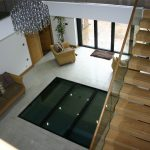 Floating staircase and glass floor section sat on a steel frame looking into basement swimming pool area.